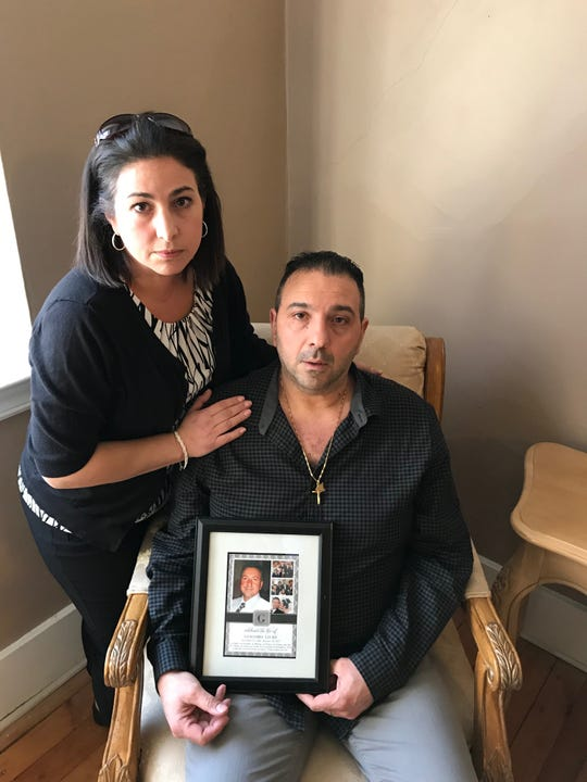 Maria and Ray Lo Re of Webster holding a photo of his father, Giacomo Lo Re, who died in 2017.