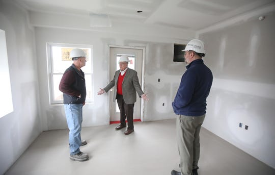 Nelson Leenhouts, founder and chairman of Home Leasing, center, and his newly appointed CEO, Bret Garwood, right, get a tour of a second floor apartment from project manager Kevin Wuest, as Home Leasing's latest project  at Charlotte and North Union streets.