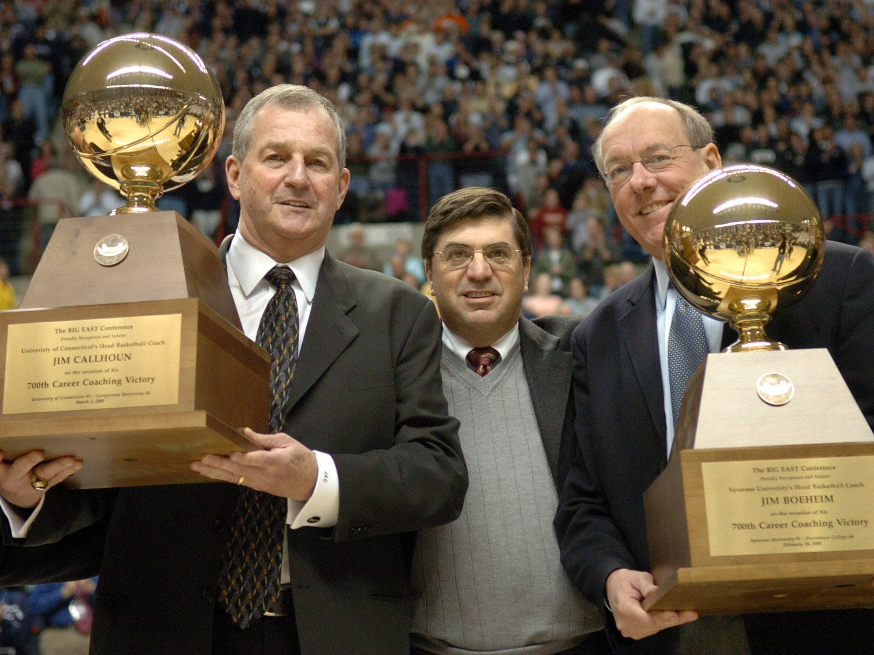 Connecticut coach Jim Calhoun, left, and Syracuse coach Jim Boeheim, flank Big East Commissioner Mike Tranghese after they were presented with their trophies for coaches with 700 wins, before the start of a game in Storrs, Conn., in this March 5, 2005 photo.