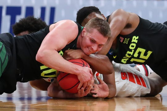 Elijah Hughes of the Syracuse Orange fights for the ball against Makai Mason (10) and Jared Butler (12) of the Baylor Bears during the first half in the first round of the 2019 NCAA Men's Basketball Tournament at Vivint Smart Home Arena on March 21, 2019 in Salt Lake City, Utah.