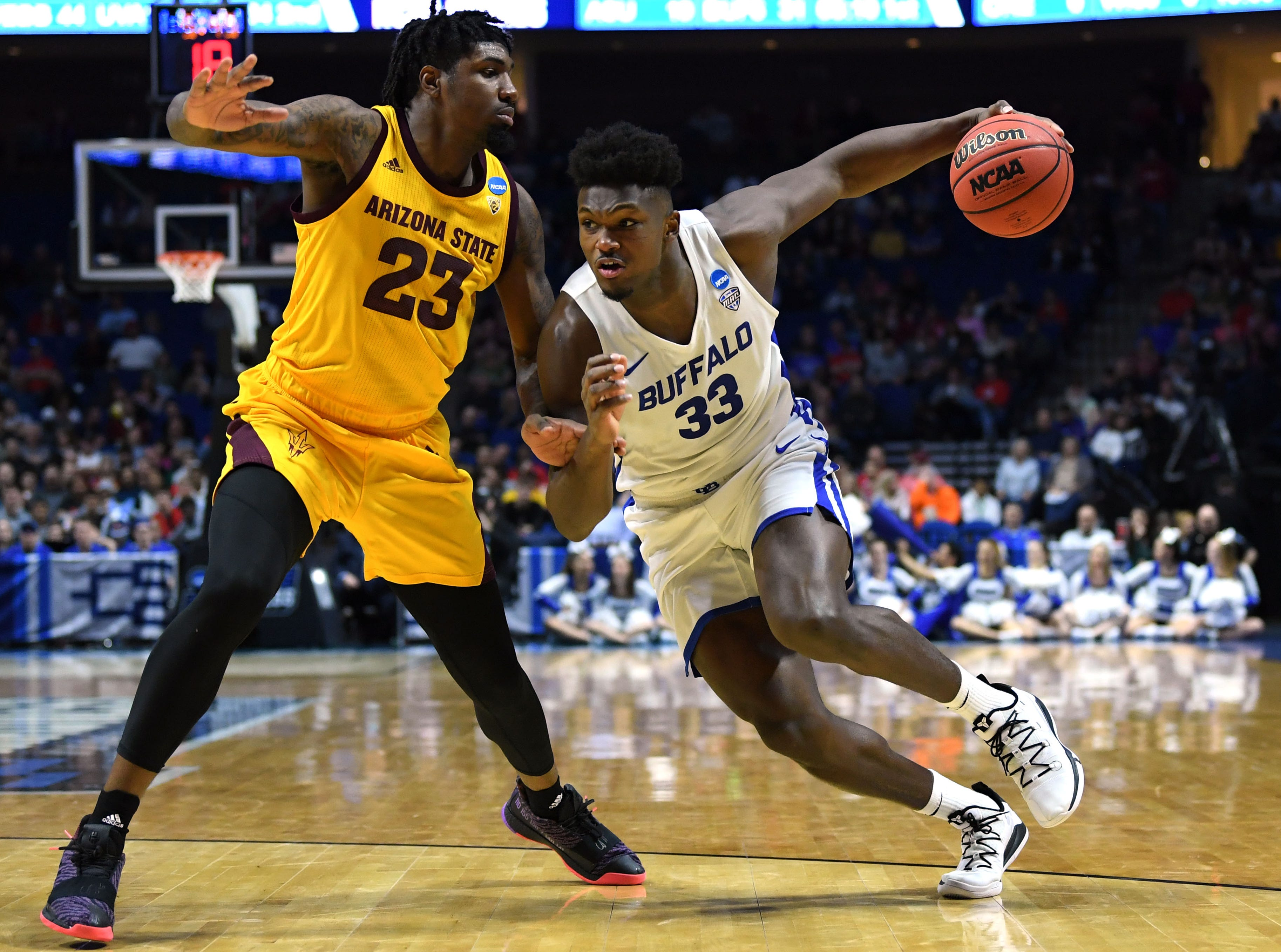 TULSA, OKLAHOMA - MARCH 22:  Nick Perkins #33 of the Buffalo Bulls drives on Romello White #23 of the Arizona State Sun Devils during the first half of the first round game of the 2019 NCAA Men's Basketball Tournament at BOK Center on March 22, 2019 in Tulsa, Oklahoma. (Photo by Harry How/Getty Images)