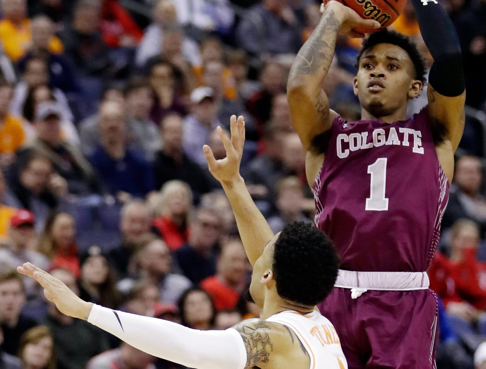 Colgate's Jordan Burns, right, shoots over Tennessee's Lamonte Turner during the first half of a first-round game in the NCAA men's college basketball tournament in Columbus, Ohio, Friday, March 22, 2019. (AP Photo/Tony Dejak)