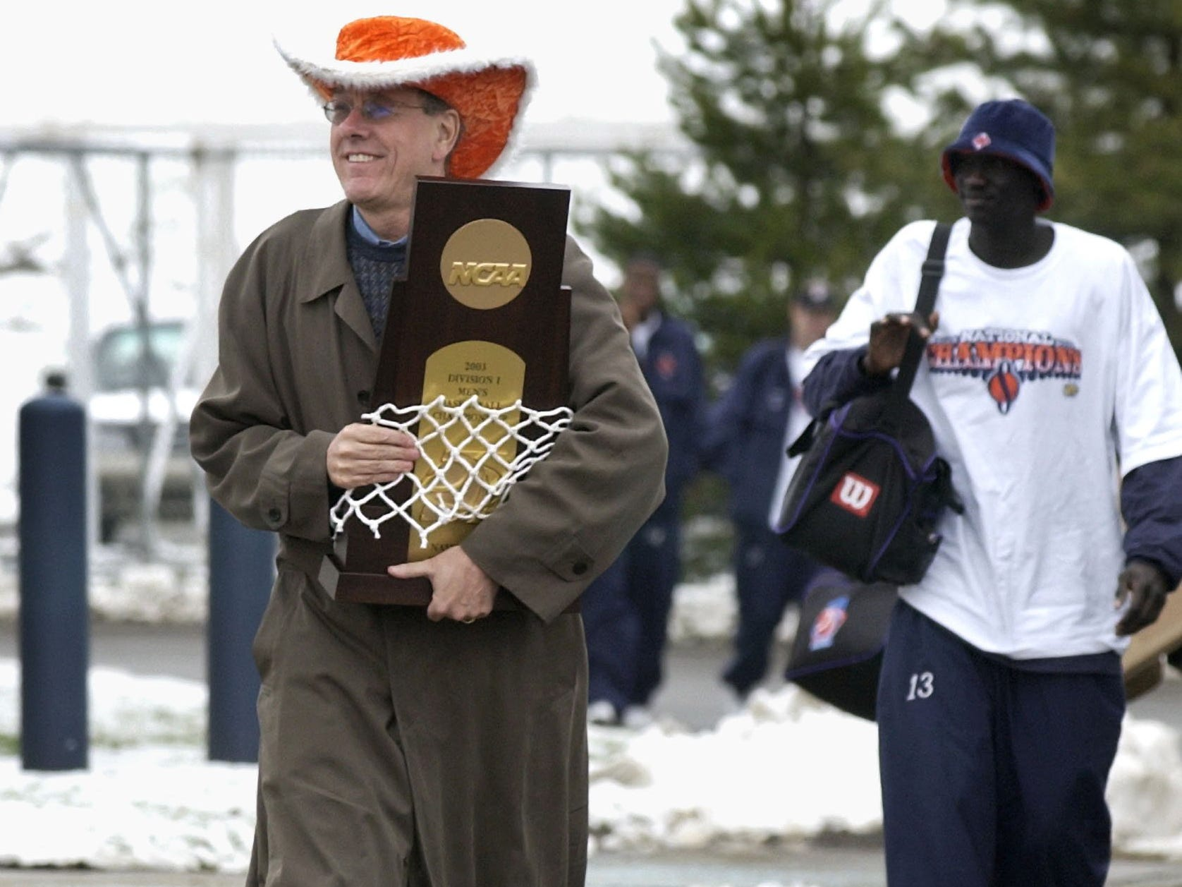 Syracuse coach Jim Boeheim leads his players while clutching the NCAA Championship trophy and net upon arriving in Syracuse on April 8, 2003. The Orangemen defeated Kansas for the national title Monday night. Senior Kueth Duany, rear, follows.