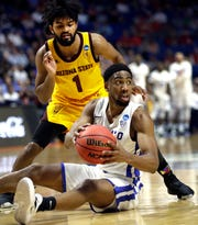 Buffalo's CJ Massinburg, bottom, looks to pass as Arizona State's Remy Martin (1) watches during the first half of a first round men's college basketball game in the NCAA Tournament Friday, March 22, 2019, in Tulsa, Okla. (AP Photo/Jeff Roberson)