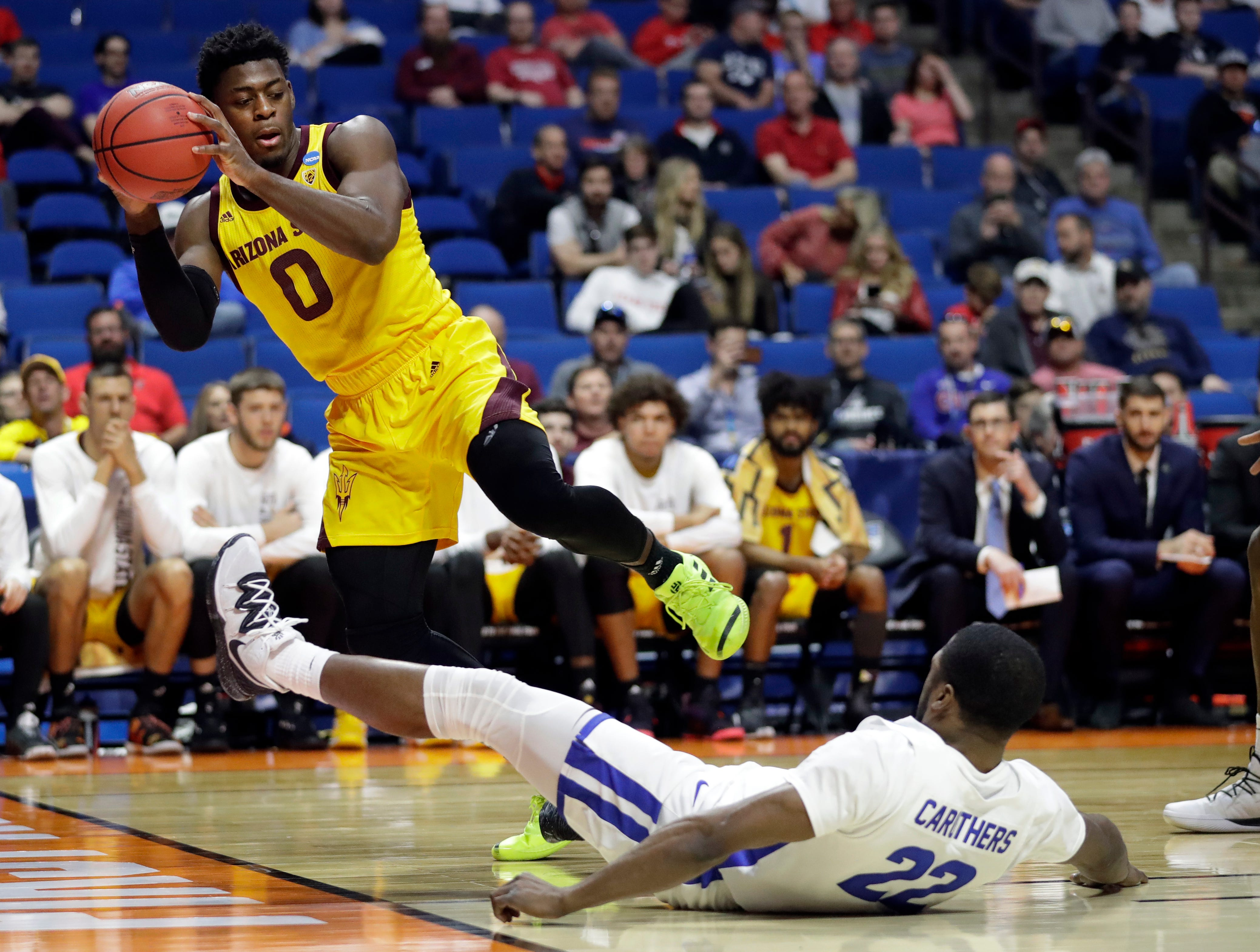 Arizona State's Luguentz Dort (0) grabs a ball before it goes out of bounds after colliding with Buffalo's Dontay Caruthers (22) during the second half of a first round men's college basketball game in the NCAA Tournament Friday, March 22, 2019, in Tulsa, Okla. (AP Photo/Jeff Roberson)
