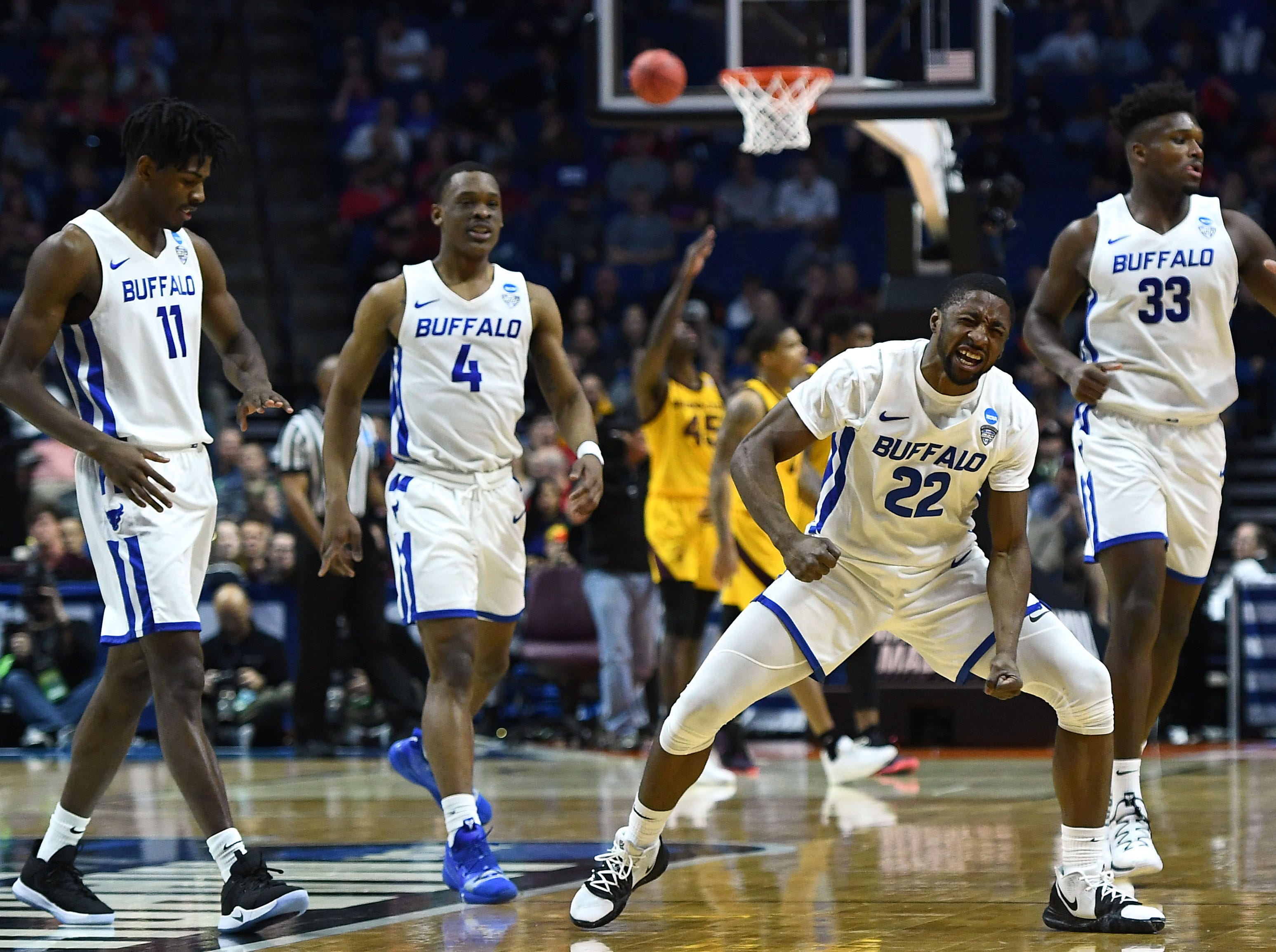 TULSA, OKLAHOMA - MARCH 22:  Dontay Caruthers #22 of the Buffalo Bulls celebrates around teammates Jeenathan Williams #11, Davonta Jordan #4, and Nick Perkins #33 during the first half of the first round game of the 2019 NCAA Men's Basketball Tournament against the Arizona State Sun Devils at BOK Center on March 22, 2019 in Tulsa, Oklahoma. (Photo by Stacy Revere/Getty Images)