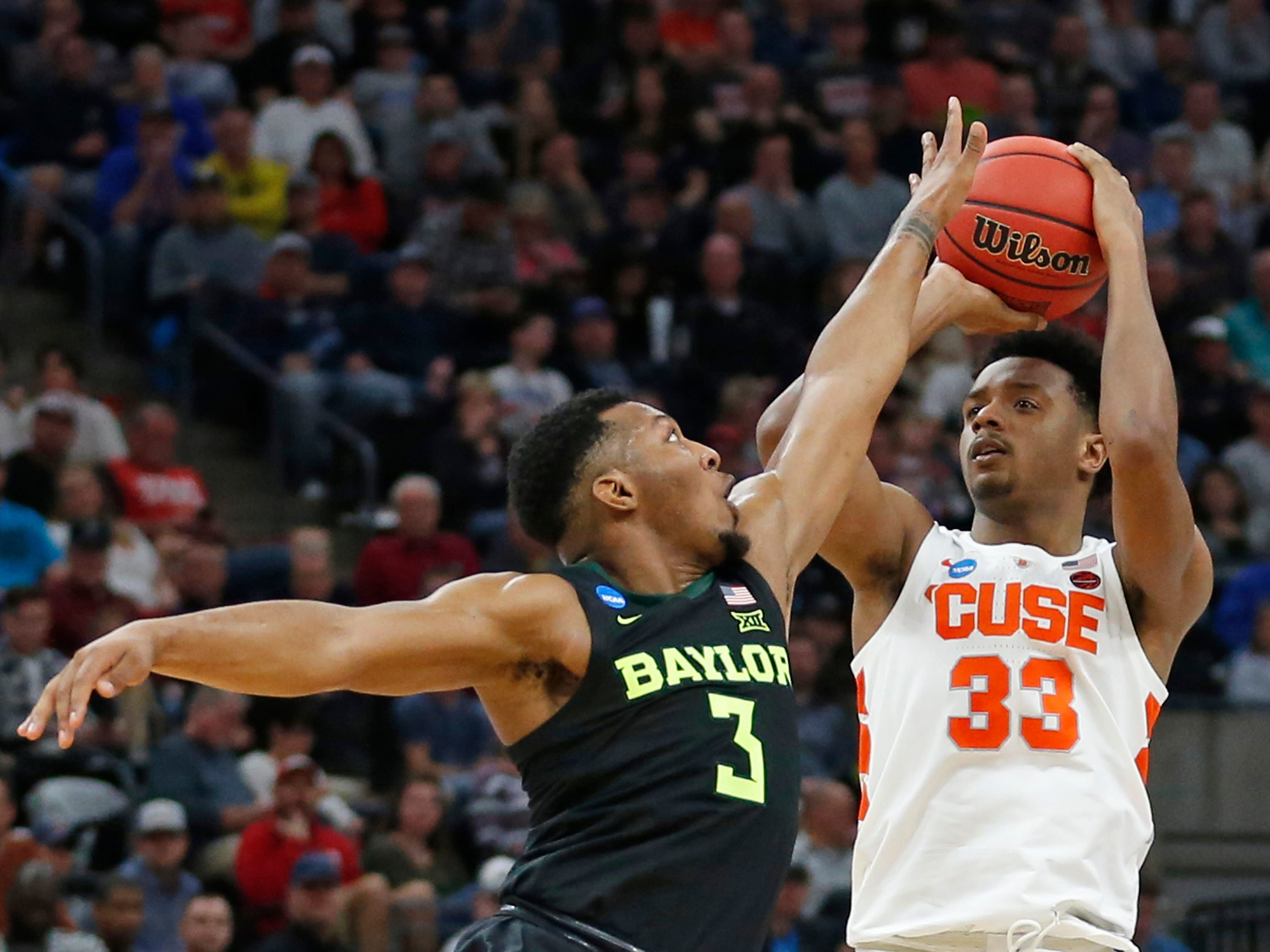 Syracuse forward Elijah Hughes (33) shoots as Baylor guard King McClure (3) defends during the first half of Thursday night's NCAA Tournament game in Salt Lake City. Hughes scored 18 points in the first half.