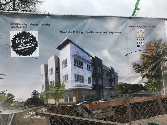 A banner of the Placer Heights mixed-use building is posted in front of the construction site in downtown Redding.