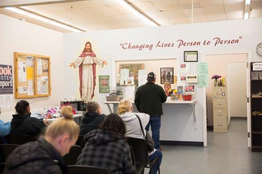 People wait to get groceries at St. Vincent de Paul food bank in Salem on March 21, 2019.
