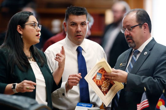 State Sens., from left, Julie C. Gonzales, D-Denver, Leroy Garcia, D-Pueblo, and Robert Rodriguez, D-Denver, confer as lawmakers convene for the new session in the Senate House chamber in the State Capitol Jan. 4, 2019, in Denver.