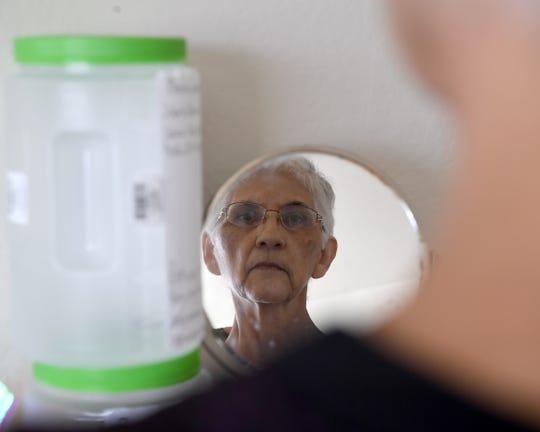 Gloria Torrez, fotografiada en su hogar en Salinas en marzo de 2019. Se le diagnosticó cáncer de estómago y solo le dieron unos cuantos meses de vida. Su familia usaba los contenedores que están junto a su espejo para recaudar fondos para los gastos funerarios de Torrez.