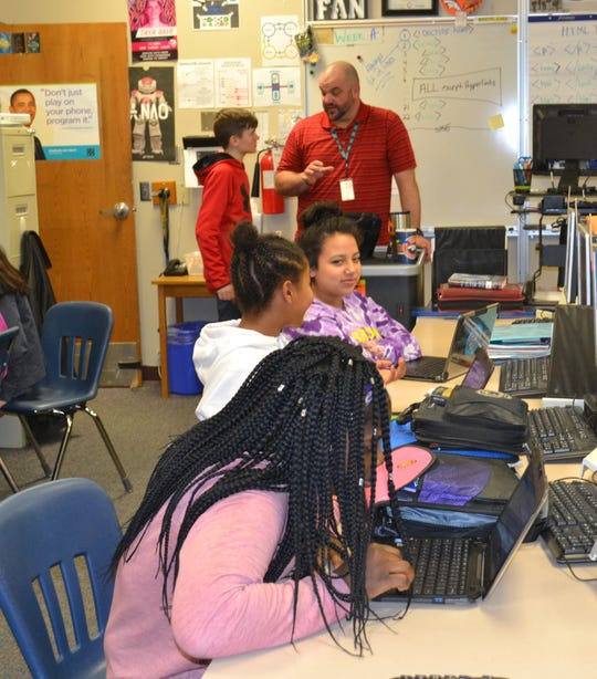 Students collaborate on video games in Jason Whiting's information and communications technology course Thursday at Patrick Henry Middle School.