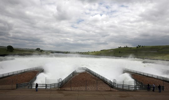 People watch water shoot out of the Oahe Dam in Pierre, S.D., Wednesday, June 8, 2011. (Devin Wagner/Argus Leader)