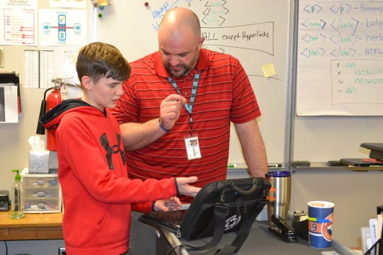 Information and Communications Technology instructor Jason Whiting talks Collin Feerick, 14, through how to create his own video game Thursday at Patrick Henry Middle School.