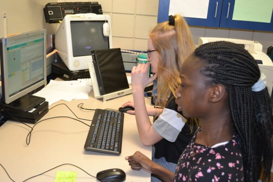 Eighth-graders Jury Okene (front) and Alyssa Lingen evaluate Lingen's video game from Jason Whiting's information and communication technology class Thursday at Patrick Henry Middle School.