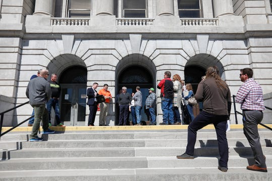 People gather on the steps of the Greene County Courthouse during an auction for properties once owned by Chris Gatley on Friday, March 22, 2019.