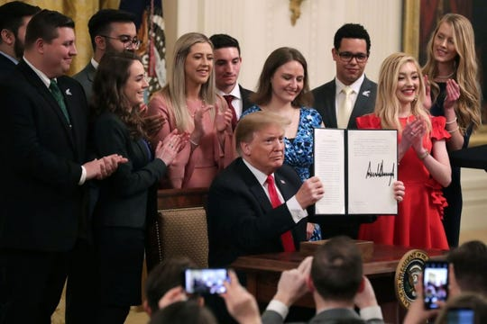 President Trump signs executive order protecting free speech on college campuses with Young Americans for Freedom members looking on.