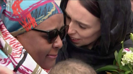 In this image made from video, New Zealand's Prime Minister Jacinda Ardern, right, hugs and consoles a woman as she visited Kilbirnie Mosque to lay flowers among tributes to Christchurch attack victims, in Wellington, Sunday, March 17, 2019. (TVNZ via AP)