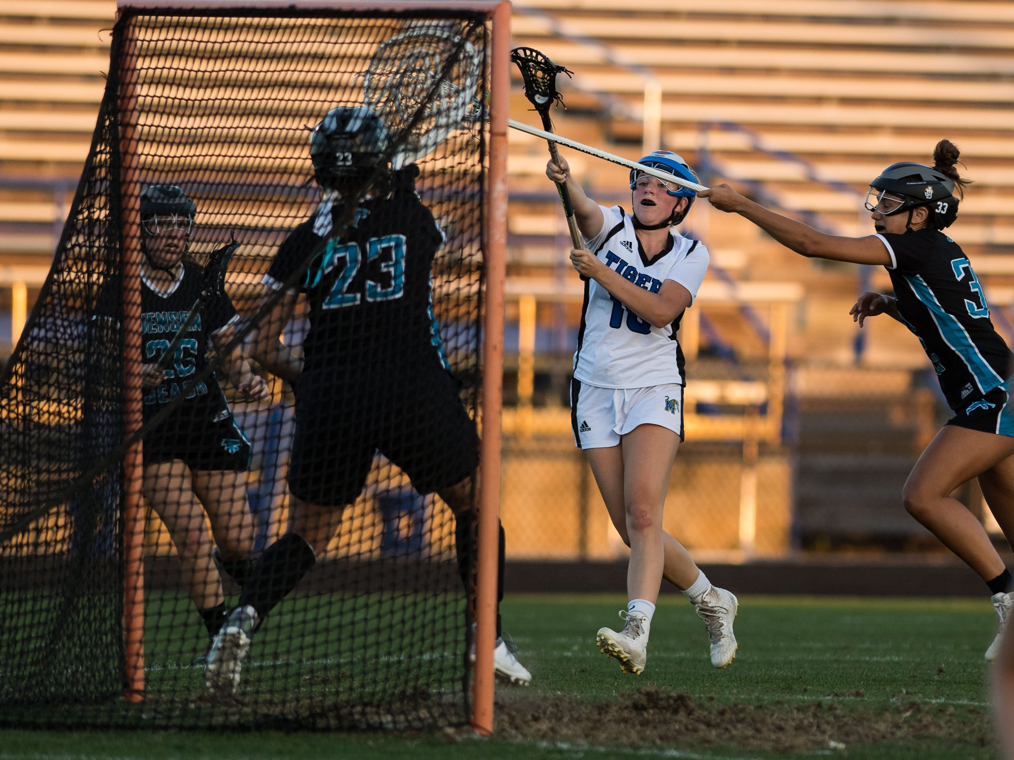 Martin County's Lauren Hooks (center) scores past Jensen Beach goalkeeper Rachel Dionne on a free-position shot, as Sandy Edwards reaches in to defend at right, during the second half of the high school girls lacrosse game Thursday, March 21, 2019, at Martin County High School in Stuart.