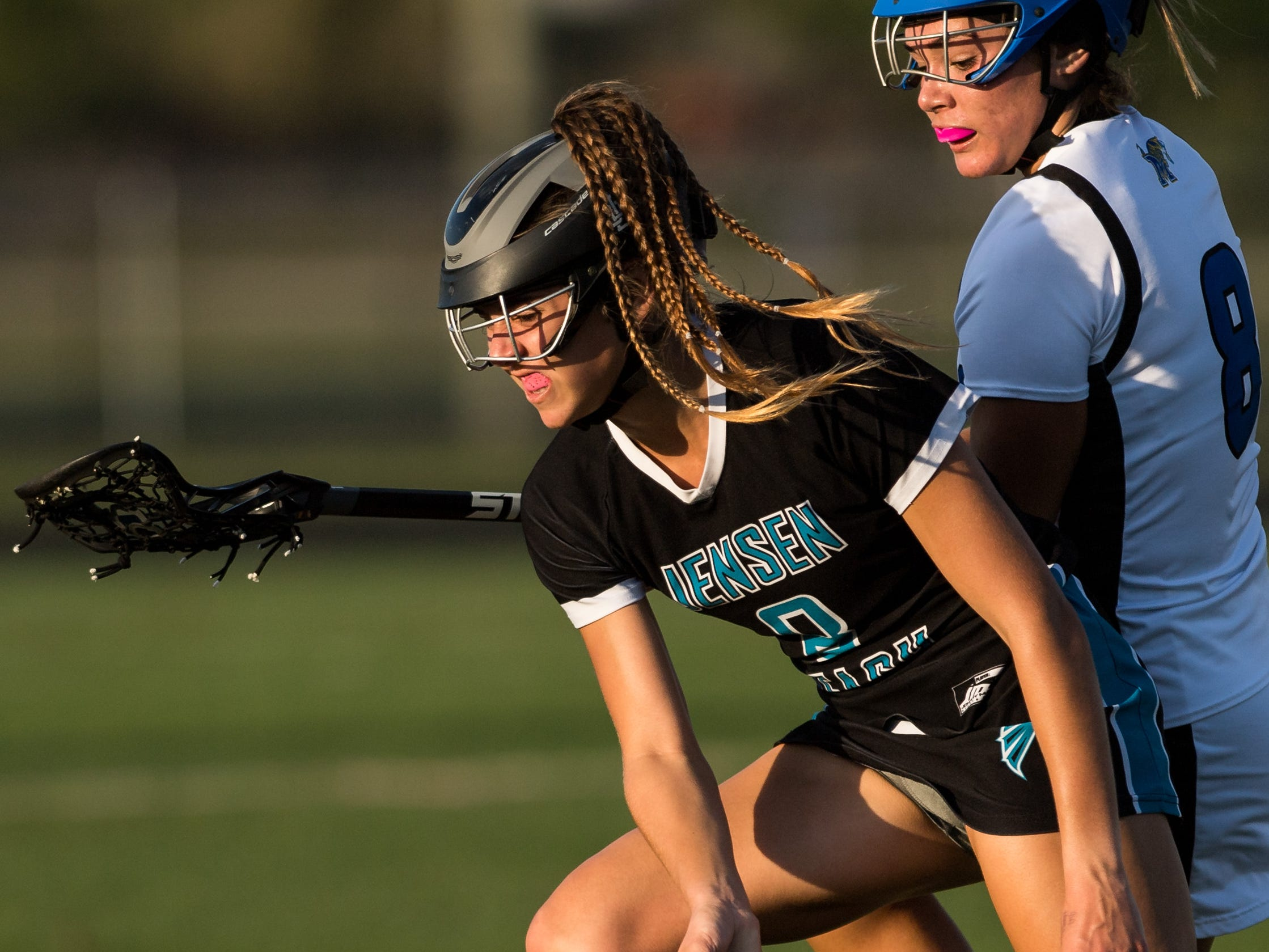Jensen Beach's Faith Hamel (left) picks up a wild ball as Martin County's Kayla Dusharm applies pressure during the first half of the high school girls lacrosse game Thursday, March 21, 2019, at Martin County High School in Stuart.
