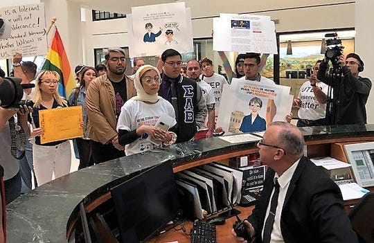 Hira Ali, leader of the We the Students Coalition at UTEP, talks to a security guard March 22, 2019, as she and others delivered a petition against the hiring of Heather Wilson as UTEP president to the Downtown El Paso building where Paul Foster, a UT System regent, has his office.