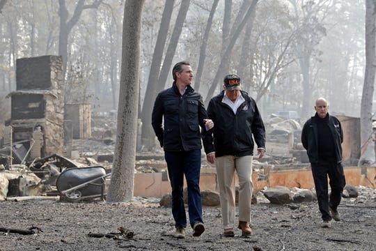 In this Nov. 17 file photo, President Donald Trump talks with California Gov.-elect Gavin Newsom, left, as California Gov. Jerry Brown, walks at right during a visit to a neighborhood destroyed by the Camp wildfire in Paradise.   Newsom is declaring a state of emergency to speed up forest management ahead of the next wildfire season, allowing fire officials to bypass certain environmental and other regulations in order to clear dead trees and vegetation more quickly.