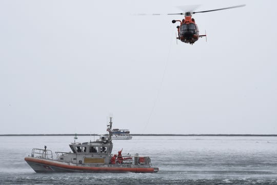 A U.S. Coast Guard Station Los Angeles-Long Beach 45-foot response boat-medium crew conducts a hoist demonstration with a Coast Guard Air Station San Francisco-Forward Operating Base Point Mugu MH-65 Dolphin helicopter crew at the Port of Los Angeles on Thursday.