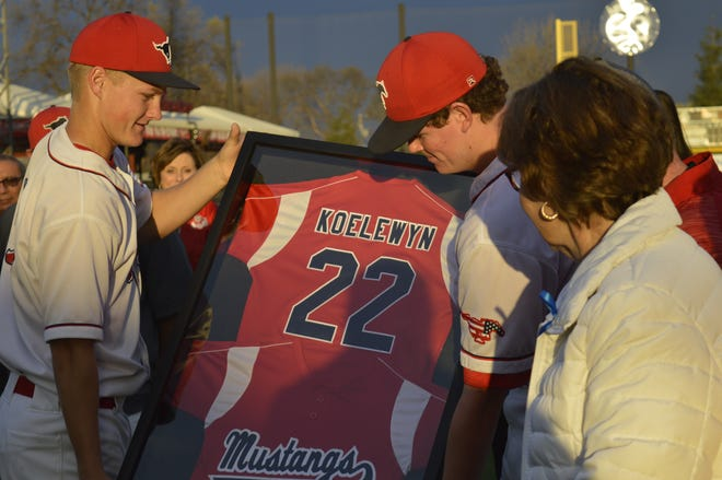 Tulare Western baseball players Levi Faucett, left, and Casey Miller present a framed No. 22 Mustangs' jersey to the Koelewyn family on Thursday at Recreation Park.