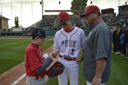 Kaleb Koelewyn, left, fist bumps Tulare Western baseball player Will Senn after receiving an autographed baseball at Recreation Park. Mustangs' head coach Ken Searcy, right, dedicated Thursday's game to Kaleb's father, Kevin, who died unexpectedly in 2018.