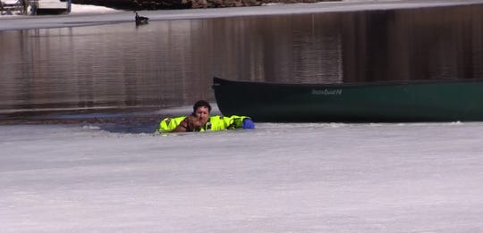 A Shawano firefighter rescues a dog that had fallen through the ice Friday afternoon on the Shawano Channel.