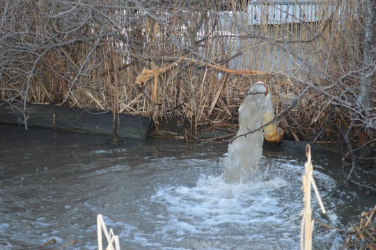 A pipe on land owned by Tompkins Mahopac Bank pumps water into Lake Mahopac on March 16, when the bank parking lot was flooded.