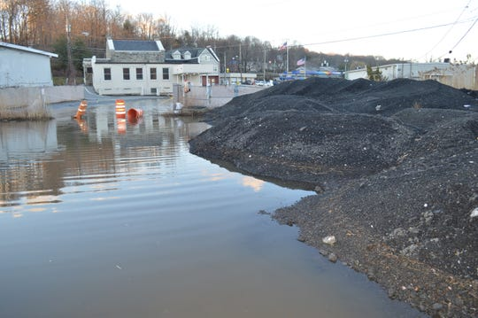 The flood that inundated Swan Cove on March 16 was at least one foot deep around asphalt millings stored on the land purchased by the town for $1 million.