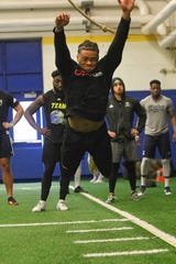 Nasir Adderley takes his turn at the long jump as nearby NFL scouts and coaches watch Blue Hen football players during drills at the University of Delaware Friday morning at Delaware Pro Day.