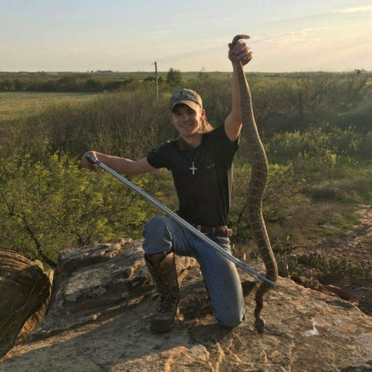 Pake Wheeler of Iowa Park holds up a large rattlesnake he caught. Wheeler is the owner of PW Snake Removal.