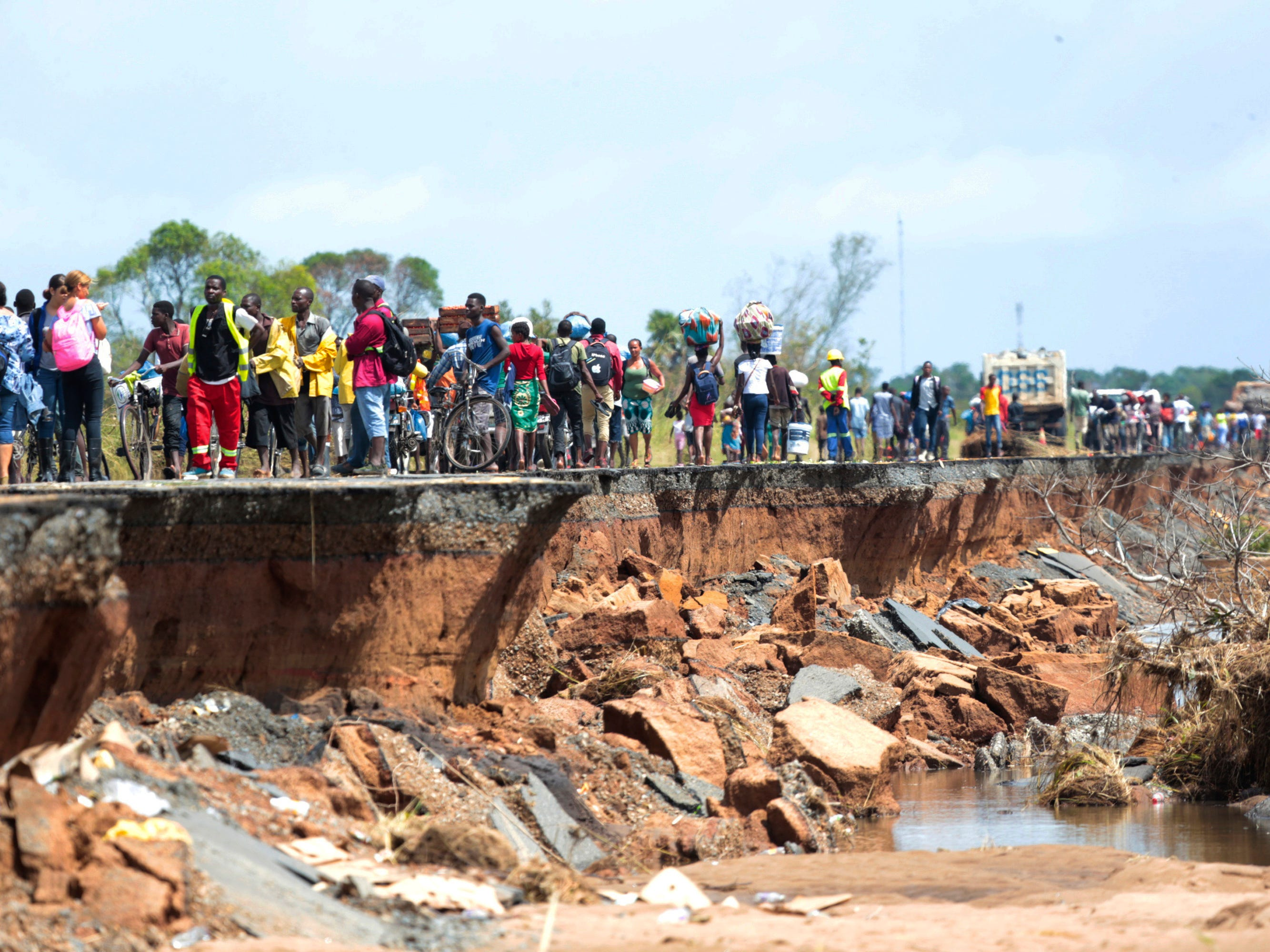 People pass through a section of the road damaged by Cyclone Idai in Nhamatanda about 50 kilometers from Beira, in Mozambique, Friday March, 22, 2019.
