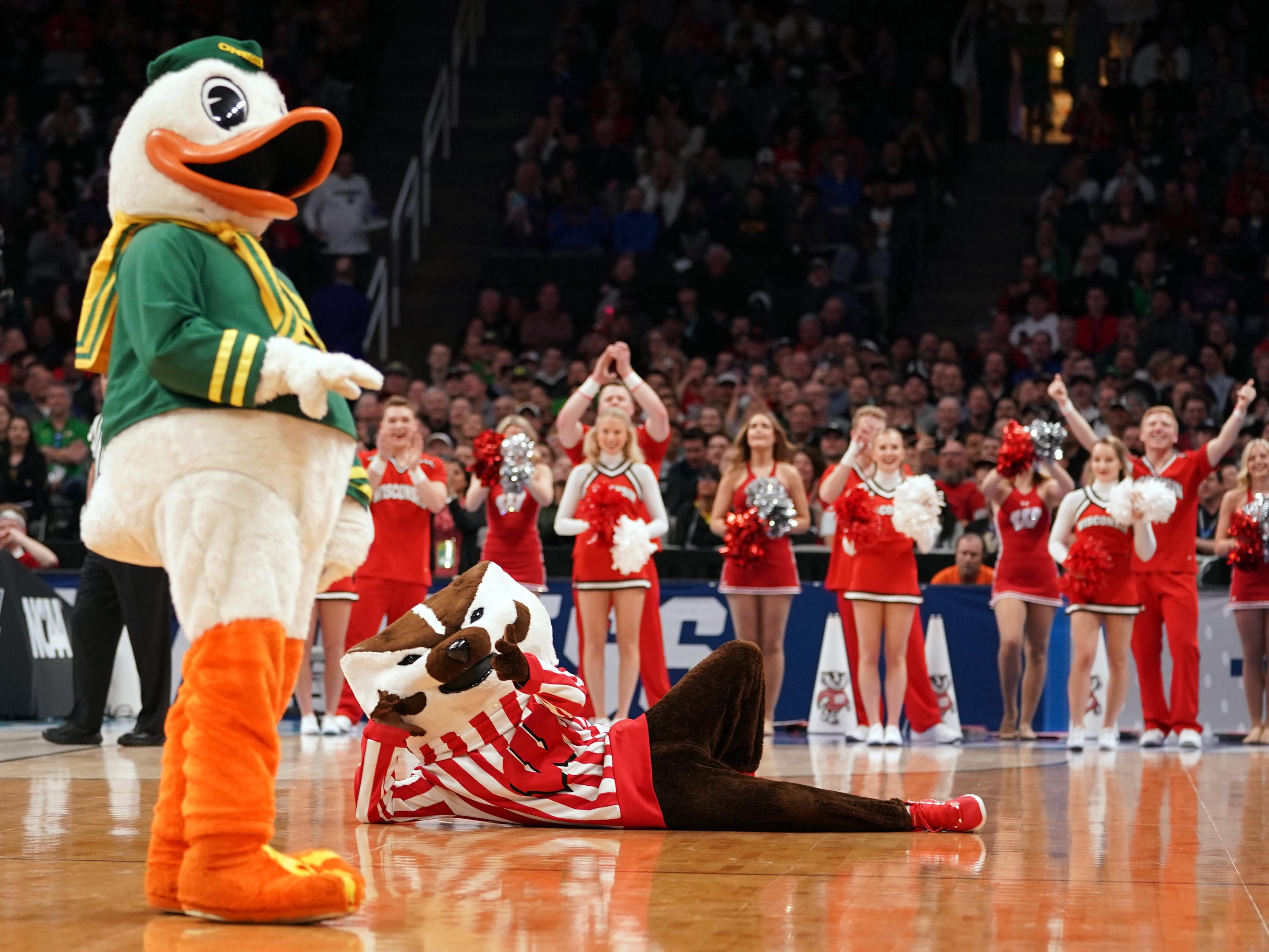 First round: The Oregon and Wisconsin mascots perform during a stoppage in play.