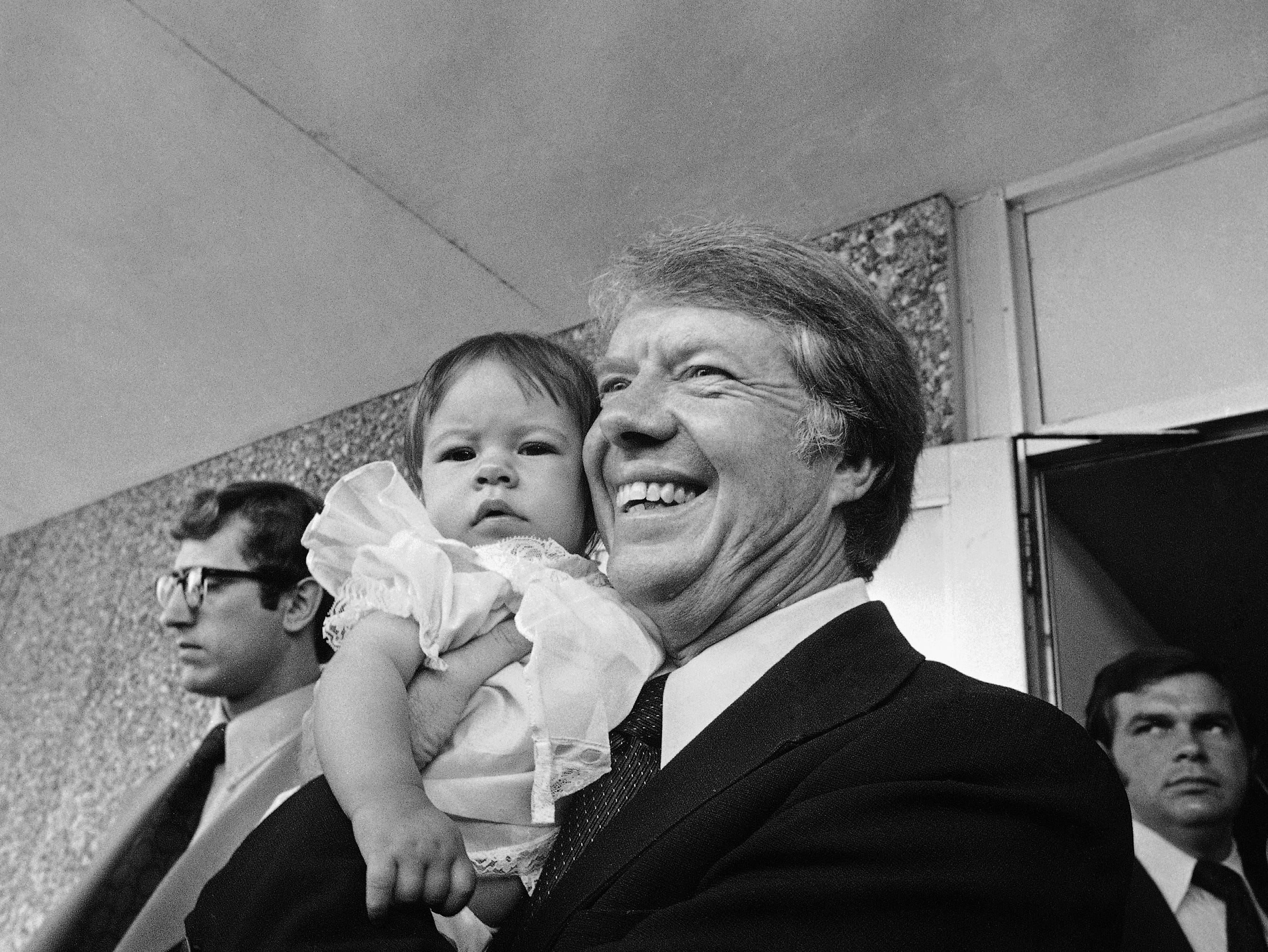 Democratic presidential candidate Jimmy Carter, right, smiles as he poses with Rachael Irene David, five months old, during a visit to Florida Memorial College in Miami, Fla., March 8, 1976.