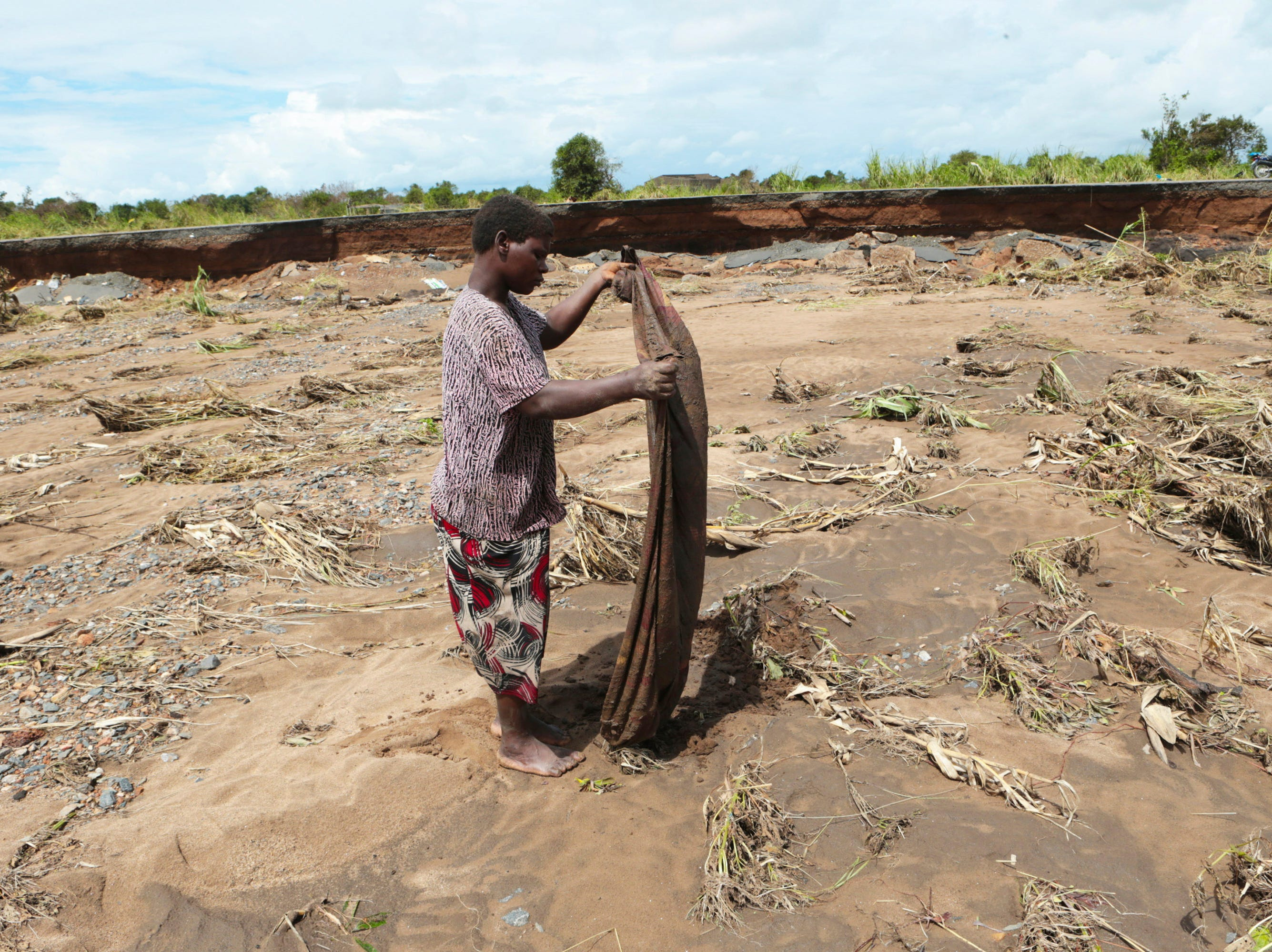 A villager salvages what remains of a piece of clothing near a section of the road damaged by Cyclone Idai in Nhamatanda about 50 kilometers from Beira, in Mozambique, Friday March, 22, 2019. As flood waters began to recede in parts of Mozambique on Friday, fears rose that the death toll could soar as bodies are revealed.
