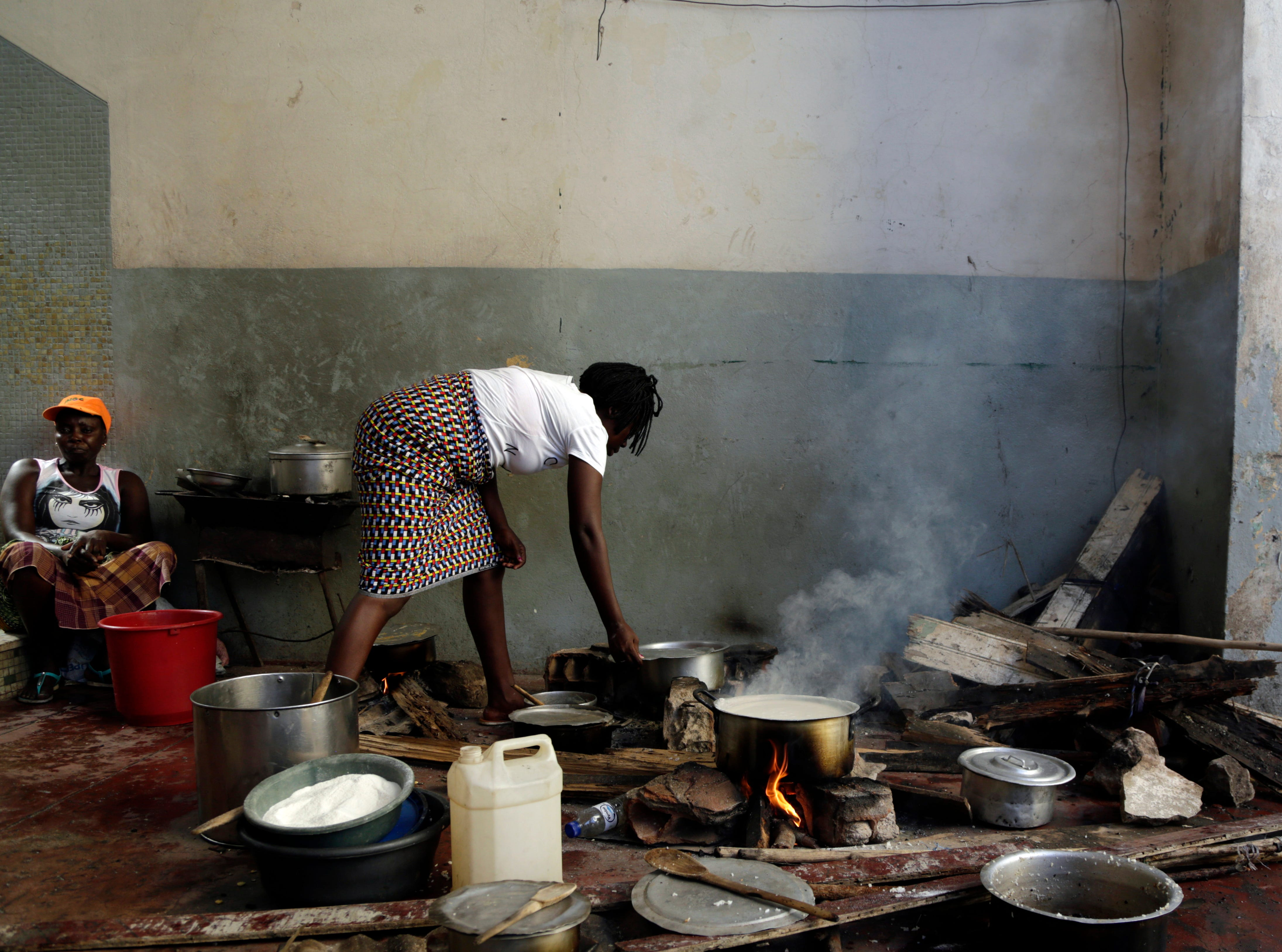 A woman cooks on the floor at a displacement centre in Beira, Mozambique, Friday, March 22, 2019.