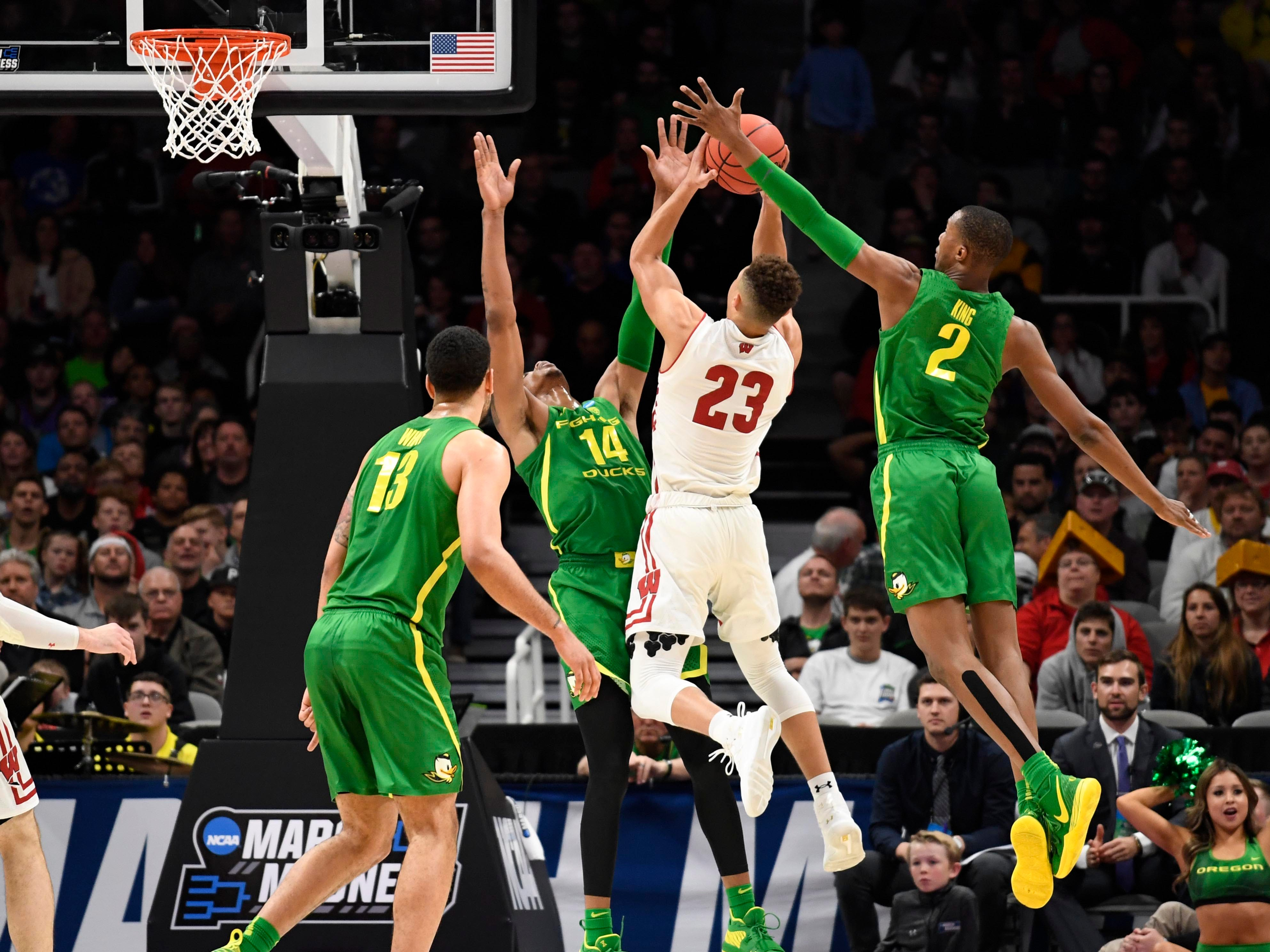First round: Wisconsin guard Kobe King shoots while being defended by Oregon forwards Louis King and Kenny Wooten during the Ducks' win over the Badgers.