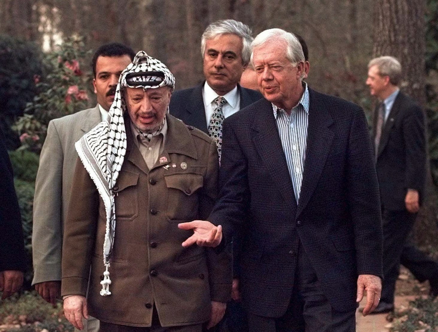 Jimmy Carter talks with Palestinian leader Yasser Arafat as they walk down a path at the Carter home in Plains, Ga.,  March 5, 1997.