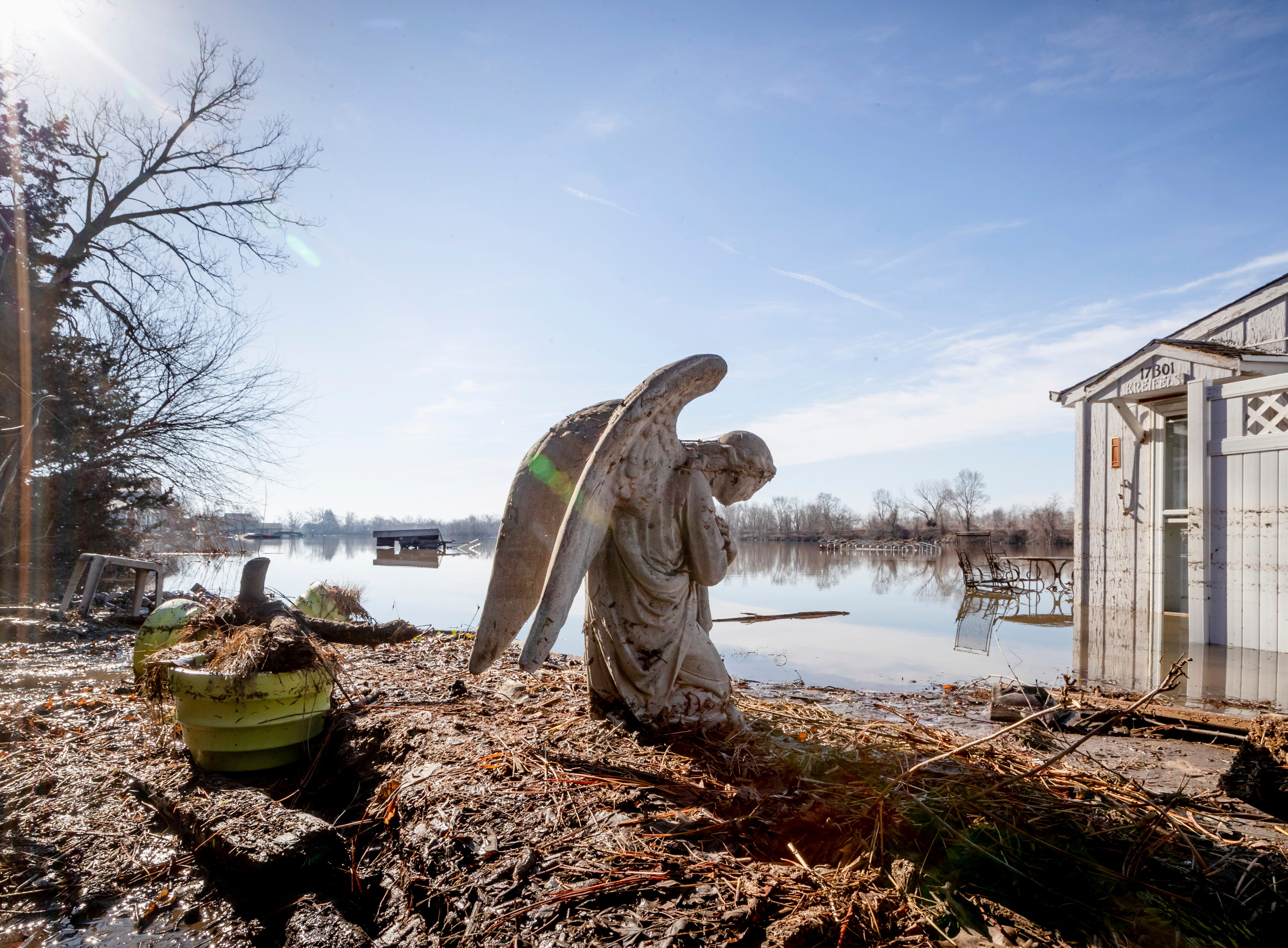 An angel statuary graces a yard near Hansen Lake Friday, March 22, 2019, in Bellevue, Neb. Residents were allowed into the area for the first time since floodwaters overtook several homes. Flooding in Nebraska has caused an estimated $1.4 billion in damage. The state received Trump's federal disaster assistance approval on Thursday.