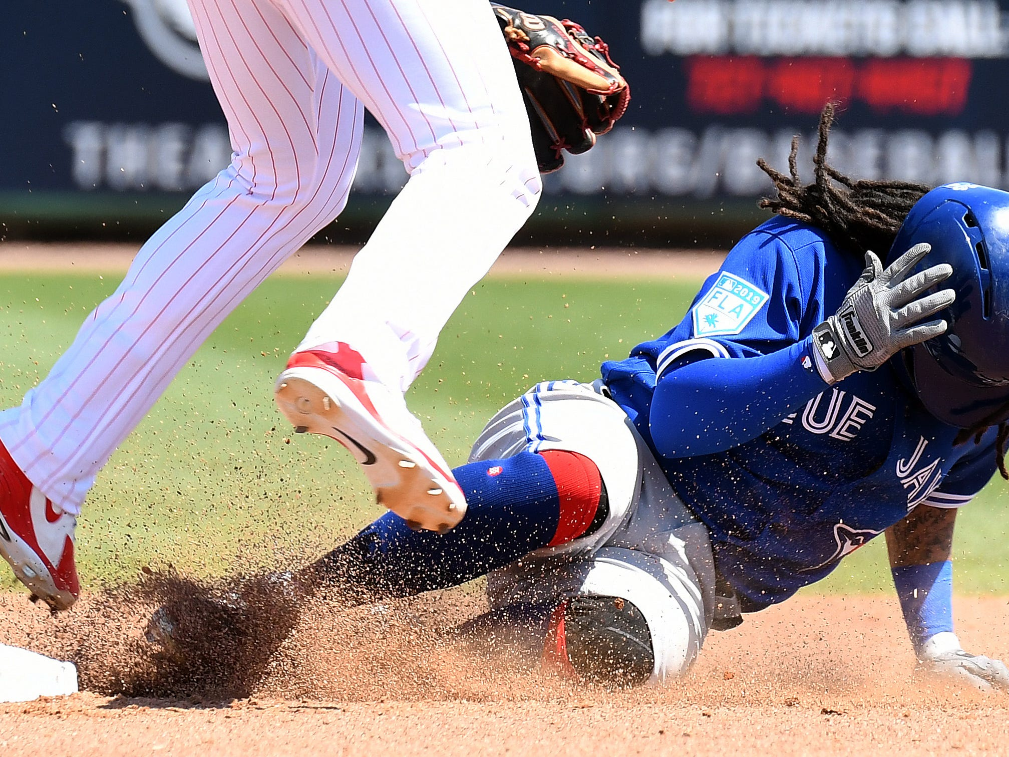 March 21: Blue Jays infielder Freddy Galvis ducks as Philadelphia's Cesar Hernandez tries to turn a double play.
