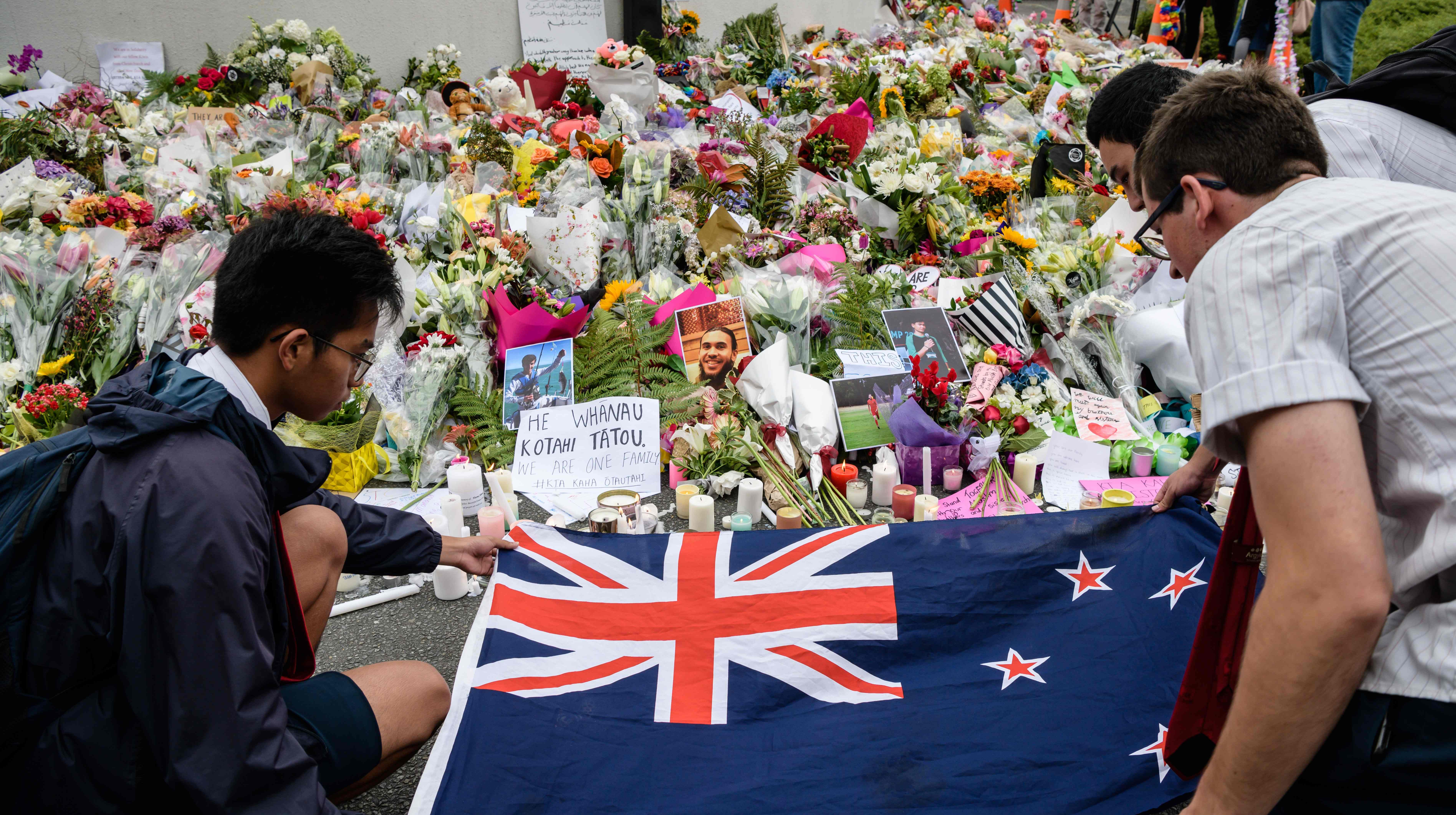 Students display the New Zealand national flag next to flowers during a vigil in Christchurch on March 18, 2019, three days after a shooting incident at two mosques in the city that claimed the lives of 50 Muslim worshippers.