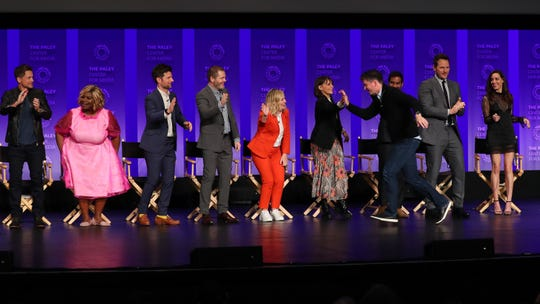 "Rob Lowe, Retta, Adam Scott, Nick Offerman, Amy Poehler, Michael Shur, Rashida Jones, Aziz Ansari, Chris Pratt, Aubrey Plaza, and Jim O'Heir high five at the ""Parks and Recreation"" 10-year anniversary reunion at PaleyFest."