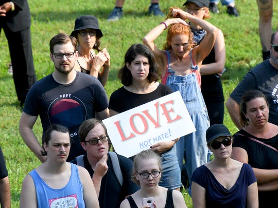 "A person holds a ""Love not hate!"" sign at a rally held at Booker T. Washington Park in Charlottesville, Virginia, on August 12, 2018."
