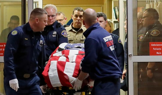 The body of a Kittitas County Sheriff's deputy is draped with a U.S. flag as it is carried out of Kittitas Valley Healthcare Hospital in the early morning hours of Wednesday, March 20, 2019, in Ellensburg, Wash. An undocumented immigrant killed a sheriff's deputy and injured a police officer after an exchange of gunfire during an attempted traffic stop.