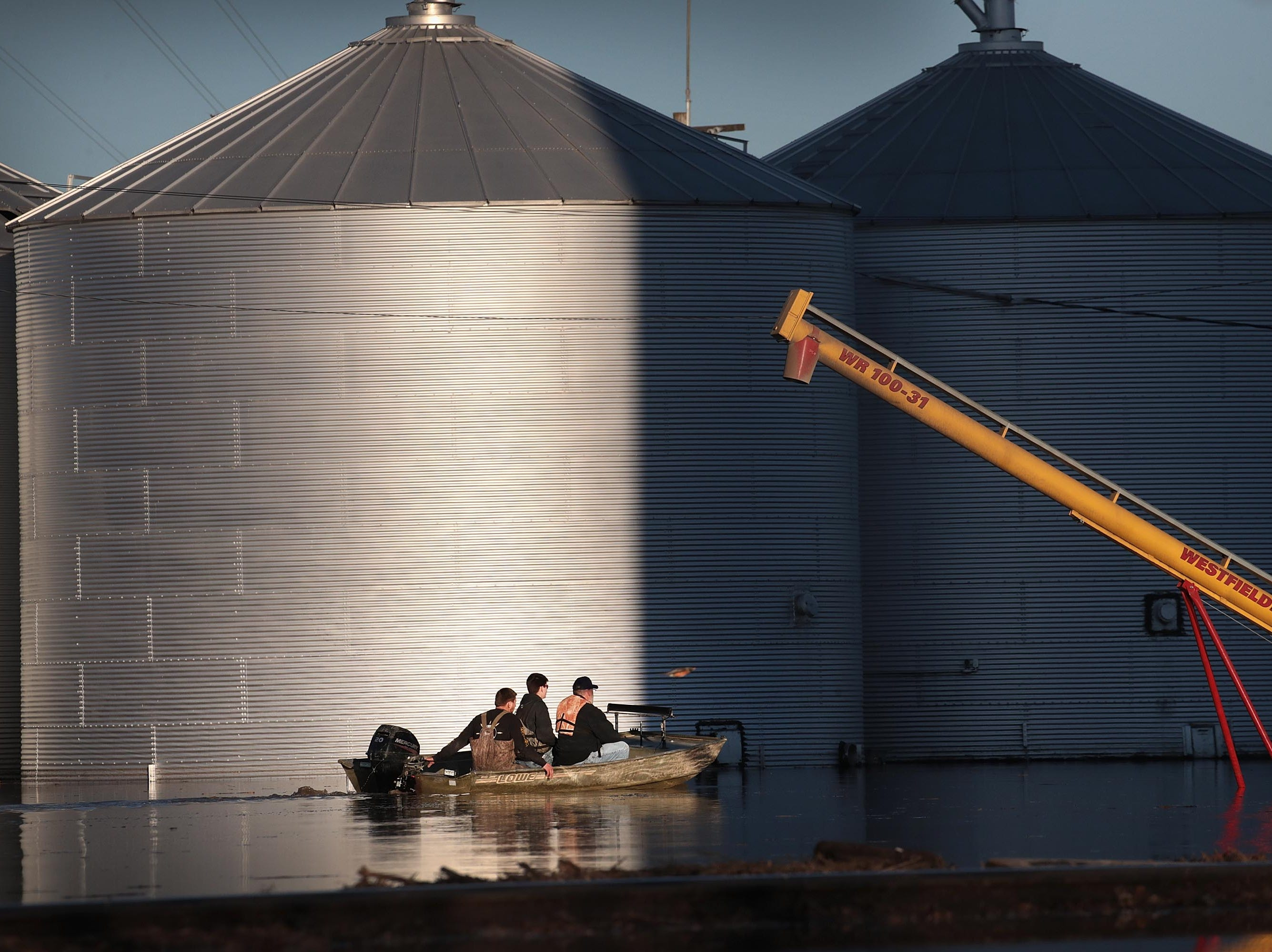 """A boat passes by grain bins which are surrounded by floodwater on March 21, 2019 in Craig, Mo. The town of Craig is completely surrounded by floodwater. Several Midwest states are battling some of the worst flooding they have experienced in decades as rain and snow melt from the recent """"bomb cyclone"""" has inundated rivers and streams. At least three deaths have been linked to the flooding."""