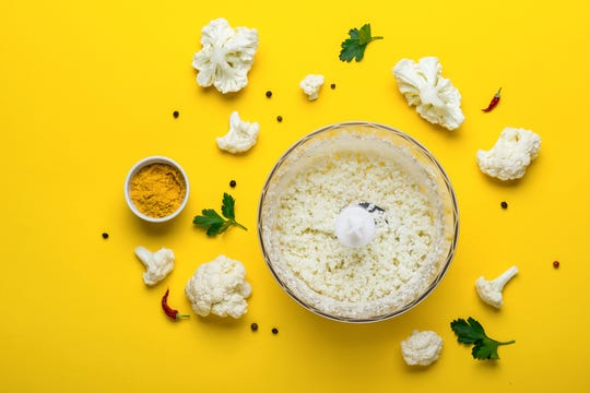 Blender bowl with freshly prepared cauliflower rice and spices on yellow background.