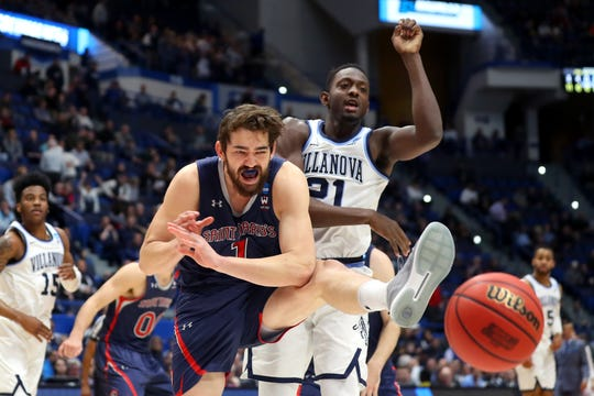 Jordan Hunter of the Saint Mary's Gaels and Dhamir Cosby-Roundtree #21 of the Villanova Wildcats compete for a rebound in the first half during the first round of the NCAA tournament.